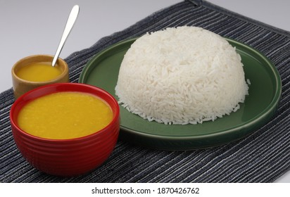 This is a Indian meal called Dal Chaval,the rice is served on a green plate and the dal is served in a red bowl with ghee in an ocher bowl with stainless steel spoon and all this placed on a blue mat.