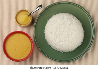 This is a Indian meal called Dal Chaval,the rice is served on a green plate and the dal is served in a red bowl and ghee in an ocher bowl with stainless steel spoon and all this placed on a beige mat.