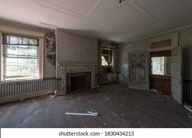 This is an interior view of a bedroom with radiators, fireplace, windows, and door at the long-abandoned and historic Dunnington Mansion in Farmville, Virginia.