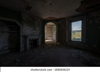 This is an interior view of a corner bedroom with a fireplace at the long-abandoned and historic Dunnington Mansion in Farmville, Virginia.
