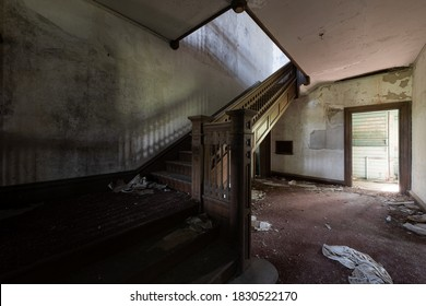 This is an interior view of the first floor foyer with a stunning wood paneled staircase at the long-abandoned and historic Dunnington Mansion in Farmville, Virginia.