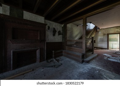 This is an interior view of the first floor foyer with a brick fireplace and stunning wood paneled staircase at the long-abandoned and historic Dunnington Mansion in Farmville, Virginia.
