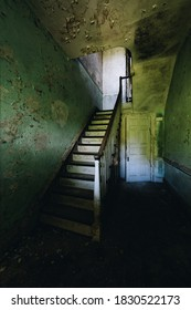 This is an interior view of a skinny staircase at the long-abandoned and historic Dunnington Mansion in Farmville, Virginia.
