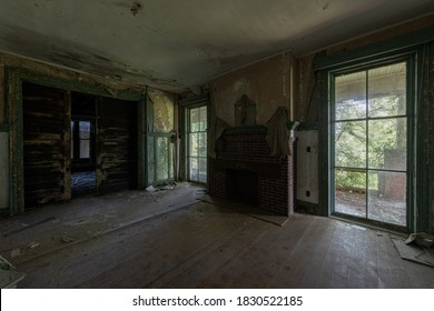 This is an interior view of tall and wide glass windows in the formal dining room at the long-abandoned and historic Dunnington Mansion in Farmville, Virginia.