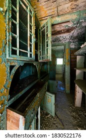 This is an interior view of unique arched and glass-enclosed shelving in the laundry room at the long-abandoned and historic Dunnington Mansion in Farmville, Virginia.