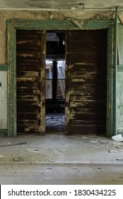 This is an interior view of wood pocket doors at the long-abandoned and historic Dunnington Mansion in Farmville, Virginia.