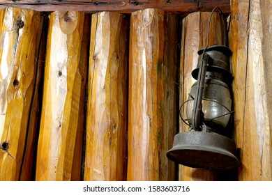 This is the interior wall of a log cabin with a rusty lantern hanging from a nail.  The logs are vertical, rustic and old looking.  This cabin was built in Minnesota during 1925.