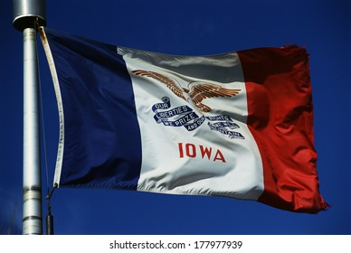 This is the Iowa State flag, waving in the wind. It is on a flagpole against a blue sky. There are three colors on the flag, the center background is white.