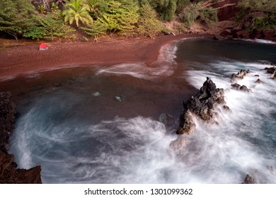 This is Kaihalulu Beach or red sand beach and is a short hike down a little path in Hana, Maui, Hawaii.