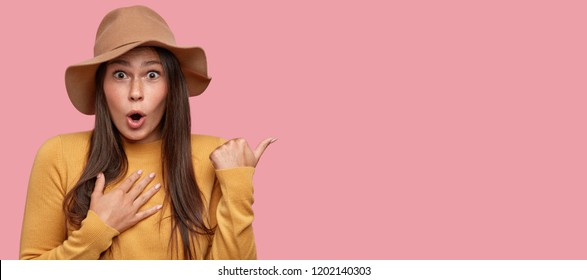 This knocks me from feet. Excited brunette young woman has bated breath, points with thumb, wears beige hat and yellow sweater, isolated over pink background with free space for your promotion