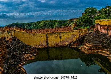 This is a landscape photo of a bawari with backgroud of aravli chain at nahargarh fort in jaipur city. bawaris are made in all old forts to storage of rain water.