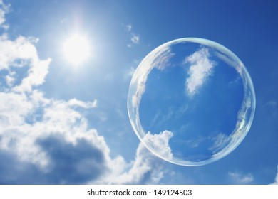 This large soap bubble floats calmly against a clear deep blue sky and clouds representing a natural 'Thought Bubble' on possible ideas for clean atmosphere, fresh air and a green environment.