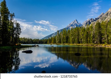 This is the Leigh Lake Trail in Grand Teton NP in Wyoming, where  beautiful reflections of sky, peaks, and forest appear upon the calm lake. One lone boulder peaks up in the center of the lake.