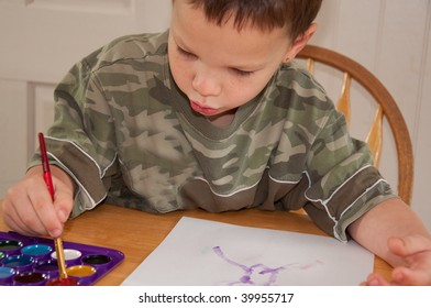This little boy is enjoying a creative moment while painting with watercolors at a table.