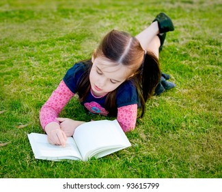 This little girl is lying on her stomach reading a book.  She looks relaxed.  Her fingers are following the text like a newer reader.  She has a look of relaxed concentration.
