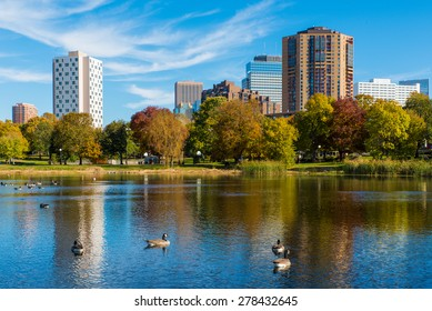 This is Loring Park in Minneapolis, Minnesota. This shows part of the skyline. This was taken during autumn. These are Canadian Geese on the lake.