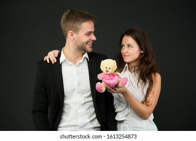 This is love. love and romance. gift with love. couple on romantic date. formal couple with toy bear. joint business. man and woman corporate attire fashion. couple in love celebrate valentines day.