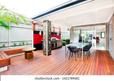 This luxury house has brick walls and a glass door from the patio side. Wooden floor made of bars of wood and the carved chairs around the table.