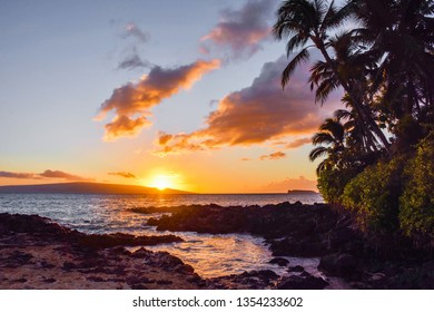This is Makena Cove Beach at Sunset in Maui Hawaii with Palm Tree Silhouettes.