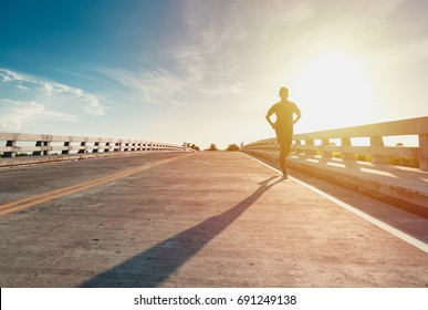 This man is jogging on street among the sun shines down light.