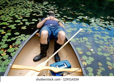 This man is shown dressed for a fishing expedition, with fishing pole, tackle box, fishing hat, and rubber boots, asleep in the back of his canoe.  Lily pads fill the water around the boat.