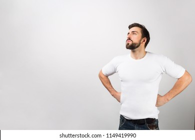 This man is standing in a position of a hero putting his hands on his hips. He is dreaming about better times or the future. That guy looks very serious. Isolated on white background.