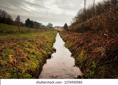 This man-made irrigation ditch carries a stream in a straight line along the side of a field a rural Wales.