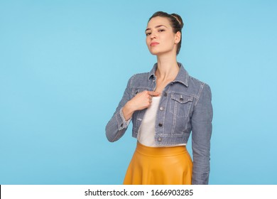 This is me! Portrait of haughty selfish fashionably dressed woman with hair bun pointing at herself, feeling proud and self-important, having big ego. indoor studio shot isolated on blue background