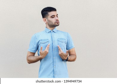 This is me. Portrait of proud handsome young bearded man in blue shirt standing, pointing, showing himself and looking with egoistic face. indoor studio shot isolated on light beige wall background.