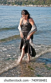 This middle aged Native American woman is wearing a formal black dress and walking barefoot in the shallow shore of the ocean.