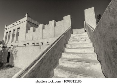 In this monochrome image, stairs lead to the roof from the courtyard of a restored traditional arabian house.