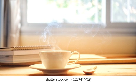 This morning a cup of hot coffee smoke and a book on wood table with window background.