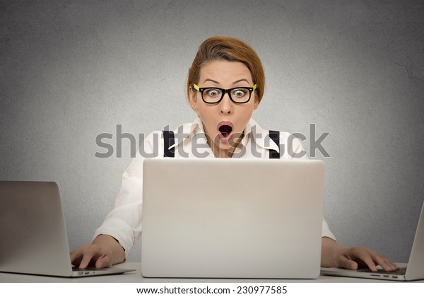This is too much! Young woman can't handle workload anymore. Busy multitasking trying to manage it all by herself working on several computers simultaneously sitting at desk in office. Face expression