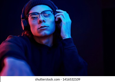 This is my favourite song. Studio shot in dark studio with neon light. Portrait of serious man.