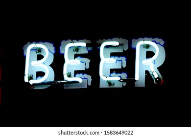This is a neon blue beer bar sign on a black background.  The neon words appear to have snow or ice decorating the edges of the words.