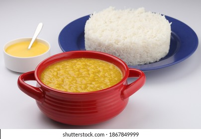 This is a North Indian dish called Dal Chaval or Dal Rice, the rice is served in a blue plate and the dal in a red serving bowl with ghee in a white bowl and all this is placed on a white surface.