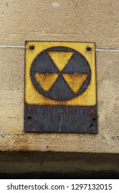 This old rusty Fallout shelter sign is a relic from the cold war, it guides to the netrance of a bomb shelter offering protection against a nuclear attack by the Russians during the cold war.