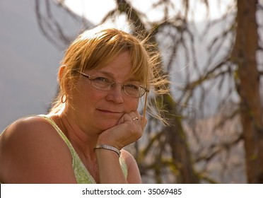 This older woman in this portrait is contemplative and thinking in this beauty natural setting, and herself is natural looking.