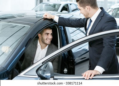 This is the one. Horizontal portrait of a handsome young businessman sitting in the car and talking to a car dealer standing near