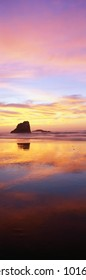 This is the Oregon coast at sunset. The large rock to the left is referred to as one of the sea stacks on the beach. The pink and blue sunset sky is reflected in the water on the beach.