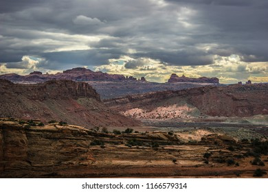This panoramic view of Arches National Park in Moab, Utah, shows the stormy sky with land formations in the distance. The sun has peeked out just enough to light up several cliffs.