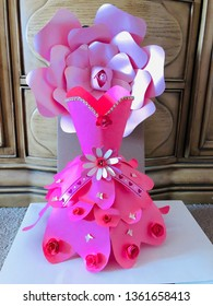 This is a paper dress.  The dress is made of cardstock paper.  The color of the dress is dark pink.  There are decorations on the dress such as laces, butterflies and flowers.
