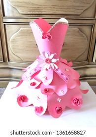 This is a paper dress.  The dress is made of cardstock paper.  The color of the dress is pink.  There are decorations on the dress such as laces, butterflies and flowers.