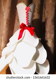 This is a paper dress.  The dress is made of cardstock paper.  The color of the dress is white.  There are row of flowers down the top and the bowl around the waist.