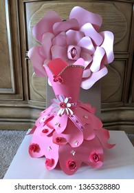 This is a paper dress.  The dress is made of cardstock paper.  The color of the dress is pink.  There are decorations on the dress such as flowers laces and butterflies.