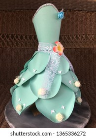 This is a paper dress.  The dress is made of cardstock paper.  The color of the dress is blue.  There are decorations on the dress such as flowers, laces and butterflies.