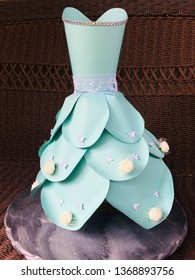 This is a paper dress.  The the dress is made of cardstock papers.  The color of the dress is blue.  There are decorations on the dress such as lace, butterflies, wrapper and flowers.