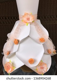 This is a paper dress.  The the dress is made of cardstock papers.  The color of the dress is white.  There are decorations on the dress such as peach lace,  orange foam flowers and plastic flowers.