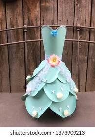 This is a paper dress.  The dress is made of cardstock papers.  The color of the dress is blue.  The dress has decoration such as laces, wrappers, butterflies and white foam flowers.