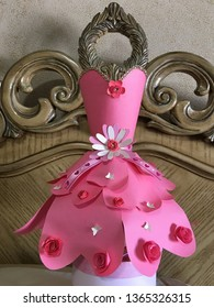 This is a paper dress.  The dress is made of cardstocks paper.  The color of the dress is pink.  There are decorations on the dress such as flowers laces and butterflies.